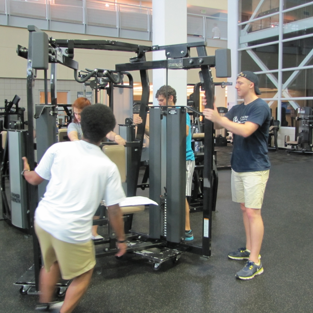 Students moving equipment on fitness floor